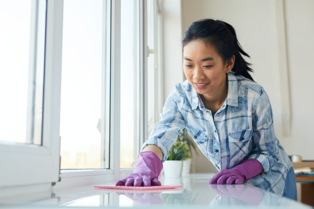 Young Asian Woman Washing Windows at Home